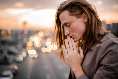 Side view of a young and handsome redhead man connecting palms near face and praying on the background of city and sunset Stock Photo