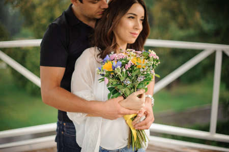 Beautiful couple in love with a bouquet of flowers standing on the green outdoors background Stock Photo