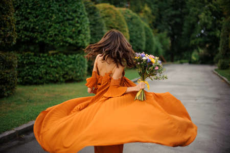 Back view of attractive woman in long orange dress with bouquet of flowers on the background of road and trees Stock Photo
