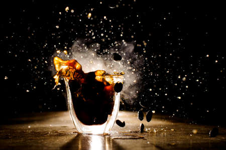Splashes of coffee from hot mug located on the wooden table on the dark background