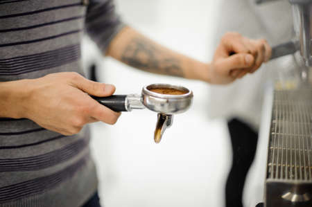 Barista with tattoo holding a temper with fresh roasted and grinded coffee on the white background