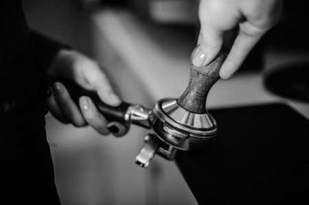 hot temper: Black and white photo of female barista using a temper to make a coffee tablet Foto de archivo