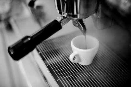 hot temper: Black and white photo of pouring coffee into a small coffee cup on the background of coffee machine Foto de archivo