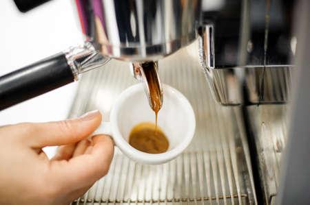 hot temper: Verter café recién hecho en una pequeña taza de café con leche en el fondo de la máquina de café Foto de archivo