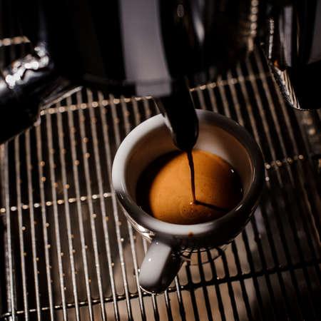 hot temper: Llenar café recién hecho en una pequeña taza de café con leche en el fondo de la máquina de café