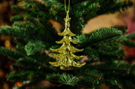christmastide: Cute Christmas tree decoration toy in the form of golden Christmas tree Stock Photo