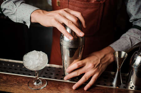 Barman in brown apron holding a shaker in hands behind the bar counter on the indoors background Reklamní fotografie