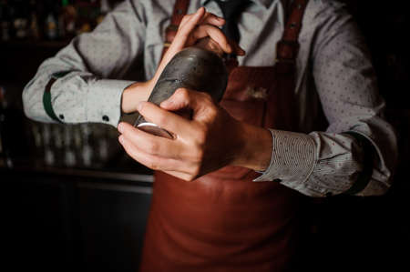 Barman in a brown apron shaking the shaker on the dark background of bar counter