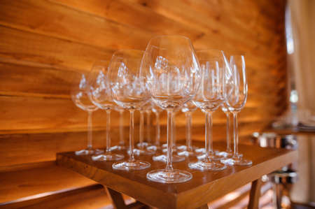 Set of washed and clean glasses for alcoholic drink arranged on the small wooden table on the light background