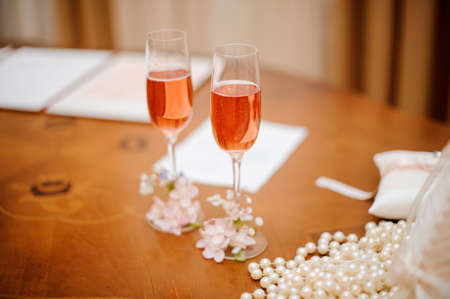 Two decorated glasses of champagne for bride and groom on the wooden table of the registry office Stock Photo