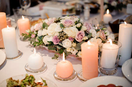 Beautiful flower composition and candles decorating a festive table covered with white tablecloth. Table decor concept