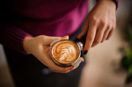 hot temper: Woman in a purple shirt holding a temper with a beautiful latte art. Coffee concept