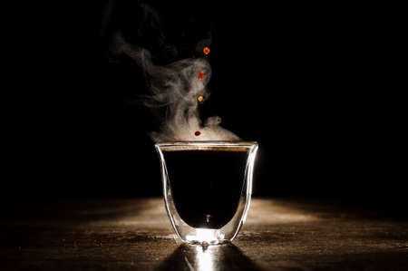 Hot coffee drink with steam spilling from clear glass coffee cup on the dark background. Coffee concept Stock Photo