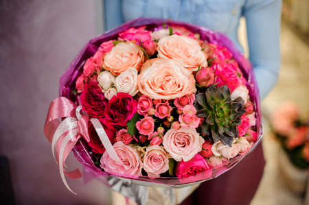Large and gorgeous pink bouquet of flowers in womans hands on the blurred background. Bouquet concept