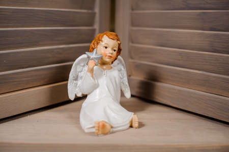 christmastide: Decorative Christmas toy in a form of the cute redhead angel sitting on the floor Stock Photo