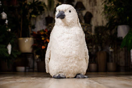 christmastide: Decorative Christmas toy in a form of the white penguin standing on the wooden floor on the background of Christmas tree Stock Photo