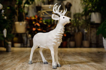 christmastide: Decorative Christmas toy in a form of the white deer standing on the wooden floor