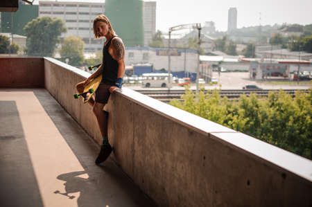 Handsome long-haired guy with tattoo sitting on the parapet and holding a longboard on the background of city Stock Photo