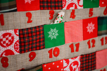 Soft textile Christmas calendar with pockets decorated with textile christmas patterns and trees hanging on the white wall