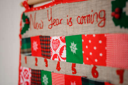 Soft and textile Christmas calendar with pockets decorated with textile christmas patterns and trees hanging on the white wall