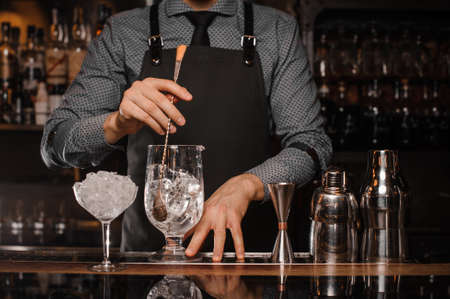Barman making a cocktail with help of the bar equipment arranged on the bar counter