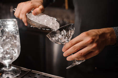 Bartender hand putting ice into the cocktail glass on the grey background on bar counter