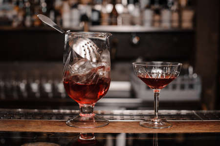 Glasses filled with red alcoholic drink arranged on the wooden bar counter against the blurred background Stock Photo