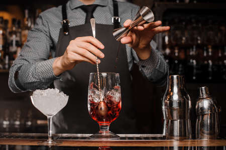 Barman in shirt and apron making an alcoholic drink with ice in a cocktail glass Banco de Imagens - 90774865