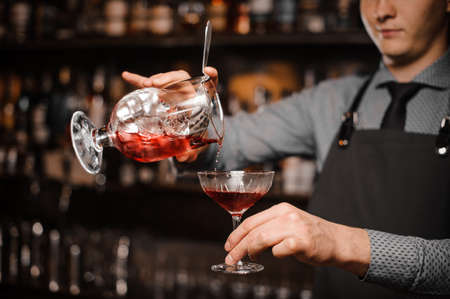 Barman pouring a red alcoholic drink into the cocktail glass against the background of bottles