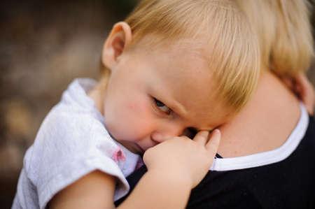 Cute blonde child lying on moms shoulder