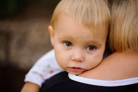 Cute little blonde and brown-eyed child dressed in white shirt lying on mother`s shoulder and looking away Stock Photo