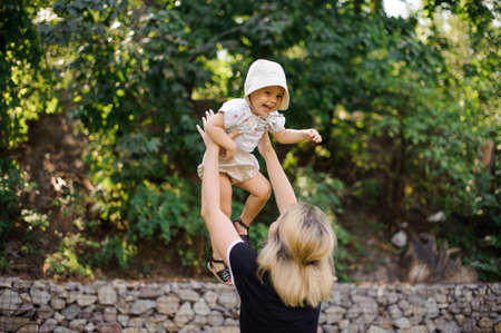 Back view of blonde mother playing with her little baby in hat on the outdoors background