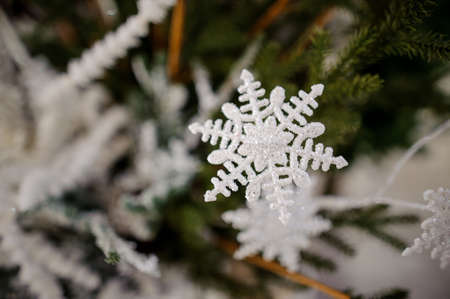 Christmas tree decoration toy in the form of a white snowflake decorated with sequins on the background of fir tree Stock Photo