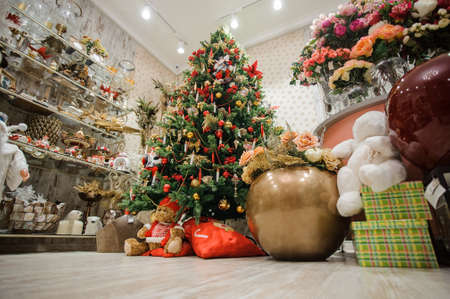 Beautiful and stylish decorated Christmas tree in a flower shop with bouquets and cute souvenirs 스톡 콘텐츠