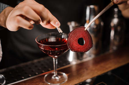 Barman decorating a cocktail glass with fresh red alcoholic drink with a slice of beet