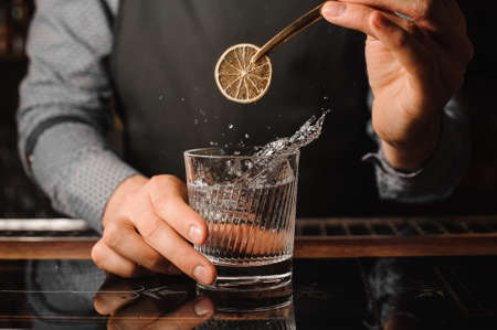 Barman decorating a clear glass filled with splashing alcoholic drink using a slice of lemon Archivio Fotografico