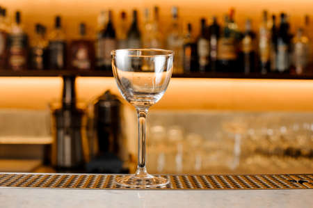 Empty and clean glass for alcoholic drink on the bar counter against the background of shelves with bottles Stock Photo