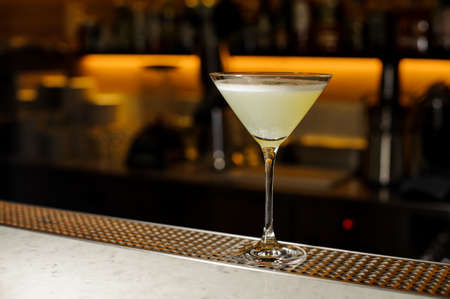 Elegant cocktail glass filled with a light fresh alcoholic drink with foam on the bar counter