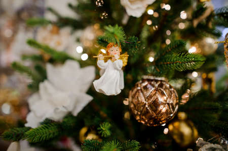 Cute toy angel with a flute and fir cone hanging and decorating a Christmas tree Stock Photo