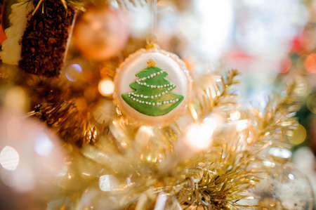 Cute ball with fir tree hanging and decorating a Christmas tree with bright garland lights