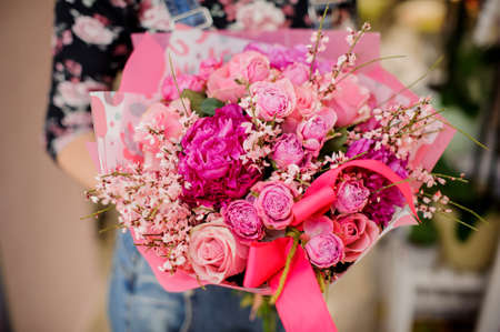 Woman holding a gorgeous flower bouquet in pink tones decorated with a bow for Valentines day