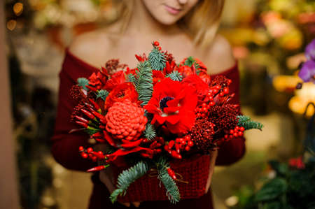 Blonde woman in a red shirt holding a beautiful bouquet of red flowers for the Valentine day