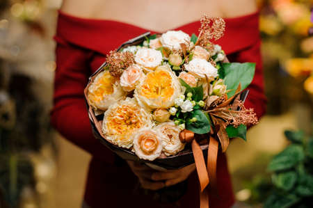 Woman in a red shirt holding a beautiful bouquet of flowers for the Valentine s day