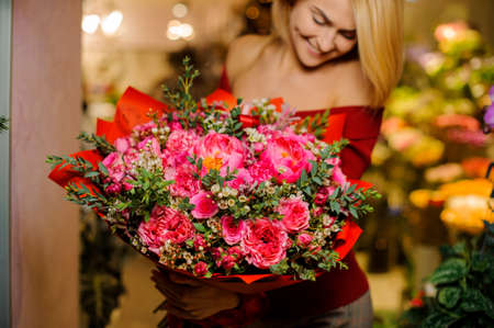 Smiling blonde girl with a large and bright pink bouquet of flowers for the Valentine s day on the blurred background