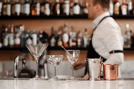 Clear and empty cocktail glasses arranged on the white bar counter against the background of barman