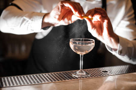 Barman hands sprinkling juice of orange peel into a glass filled with alcoholic drink on the bar counter Stockfoto