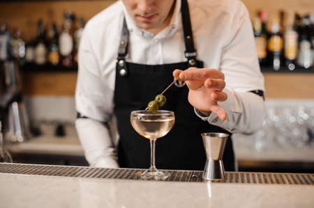 Barman adding two green olives into a glass filled with alcoholic drink on the bar counter