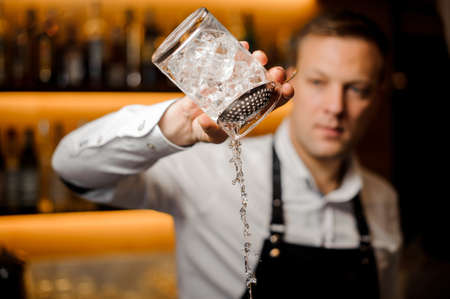 Tow-head barman at the pub pours alcoholic cocktail with ice using strainer and crystal glass Stock Photo
