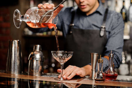 Bartender in black apron and blue shirt pours sweet cold cocktail in crystal bocal at a bar counter