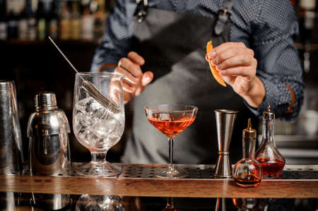 Bartender in black apron and blue shirt is going to spray an orange peel in cocktail glass at a bar counter
